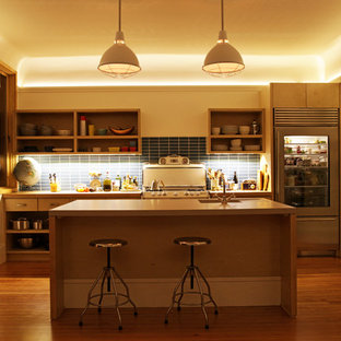 Example of a trendy galley kitchen design in San Francisco with open cabinets, light wood cabinets, concrete countertops, blue backsplash, ceramic backsplash, stainless steel appliances and an integrated sink