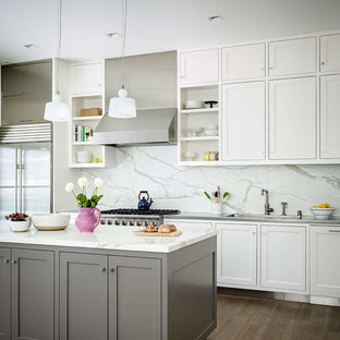 Transitional kitchen ideas - Inspiration for a transitional medium tone wood floor kitchen remodel in San Francisco with an undermount sink, shaker cabinets, white cabinets, white backsplash, stainless steel appliances, an island and marble backsplash