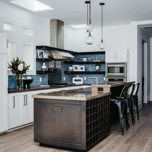 Inspiration for a mid-sized transitional l-shaped kitchen in San Francisco with granite benchtops, blue splashback, glass tile splashback, stainless steel appliances, light hardwood floors, with island, beige floor, an undermount sink and open cabinets.