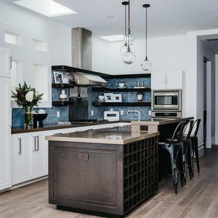 Immagine di una cucina chic di medie dimensioni con top in granito, paraspruzzi blu, paraspruzzi con piastrelle di vetro, elettrodomestici in acciaio inossidabile, parquet chiaro, isola, pavimento beige, lavello sottopiano, nessun'anta, ante in legno bruno e top marrone