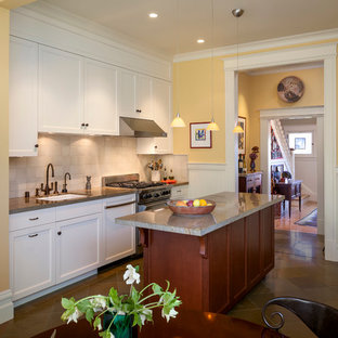 Traditional eat-in kitchen designs - Example of a classic eat-in kitchen design in San Francisco with an undermount sink, shaker cabinets, white cabinets, beige backsplash, stone tile backsplash and stainless steel appliances