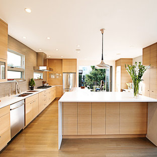 Exempel på ett avskilt modernt kök, med rostfria vitvaror, släta luckor, skåp i ljust trä, beige stänkskydd och stänkskydd i stickkakel