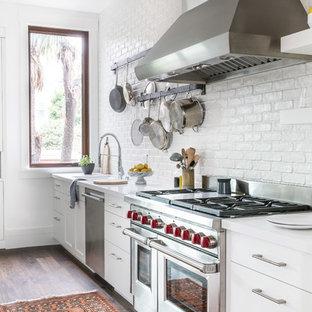Esempio di una grande cucina country con ante lisce, ante bianche, paraspruzzi bianco, paraspruzzi in mattoni, elettrodomestici in acciaio inossidabile, parquet scuro, lavello da incasso, top in quarzo composito, isola e top bianco