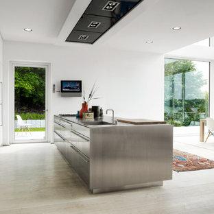 Inspiration för ett stort minimalistiskt linjärt kök med öppen planlösning, med en enkel diskho, släta luckor, vita skåp, bänkskiva i rostfritt stål, rostfria vitvaror, ljust trägolv, en köksö och beiget golv