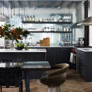 Offene Industrial Küche in L-Form mit Küchenrückwand in Metallic, Kücheninsel, Unterbauwaschbecken, flächenbündigen Schrankfronten, blauen Schränken, Marmor-Arbeitsplatte, Glasrückwand, Küchengeräten aus Edelstahl und braunem Holzboden in New York