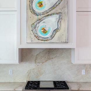 シカゴの中くらいのトラディショナルスタイルのおしゃれなキッチン (落し込みパネル扉のキャビネット、白いキャビネット、御影石カウンター、ベージュキッチンパネル、石スラブのキッチンパネル、濃色無垢フローリング、赤い床、ベージュのキッチンカウンター) の写真