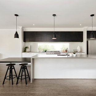 This is an example of a mid-sized contemporary single-wall eat-in kitchen in Melbourne with flat-panel cabinets, stainless steel appliances, medium hardwood floors, an island, an undermount sink and black cabinets.