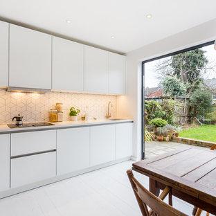 ロンドンの中サイズのモダンスタイルのおしゃれなキッチン (フラットパネル扉のキャビネット、白いキャビネット、珪岩カウンター、アイランドなし、白いキッチンパネル、黒い調理設備、塗装フローリング、白い床) の写真