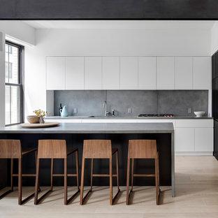 Inredning av ett modernt stort grå grått kök, med en undermonterad diskho, släta luckor, vita skåp, bänkskiva i betong, grått stänkskydd, stänkskydd i cementkakel, ljust trägolv, en köksö och beiget golv