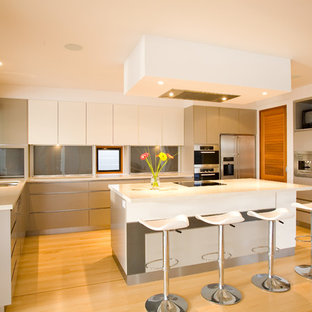 This is an example of a large contemporary l-shaped kitchen in Sunshine Coast with flat-panel cabinets, stainless steel appliances, light hardwood floors, white benchtop, an undermount sink, grey splashback, glass sheet splashback, with island, beige floor and white cabinets.