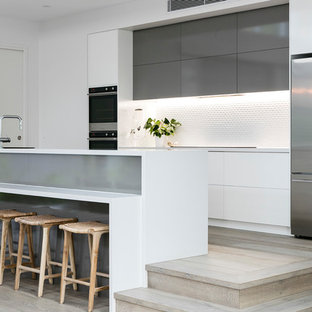 This is an example of a beach style galley kitchen in Sunshine Coast with flat-panel cabinets, white cabinets, white splashback, stainless steel appliances, light hardwood floors, a peninsula, beige floor and white benchtop.