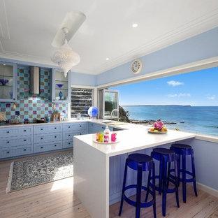 Diseño de cocina en U, marinera, abierta, con armarios con puertas mallorquinas, puertas de armario azules, salpicadero multicolor, electrodomésticos de acero inoxidable, suelo de madera clara y península