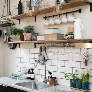 This is an example of a small country single-wall kitchen in Gothenburg with a drop-in sink, flat-panel cabinets, black cabinets, granite benchtops and no island.