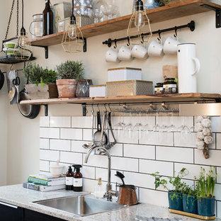 Foto de cocina lineal, rústica, pequeña, sin isla, con fregadero encastrado, armarios con paneles lisos, puertas de armario negras y encimera de granito