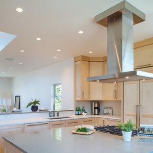 Bild på ett funkis kök, med en undermonterad diskho, skåp i shakerstil, skåp i ljust trä, bänkskiva i kvarts, stänkskydd i stenkakel, integrerade vitvaror, korkgolv och en köksö