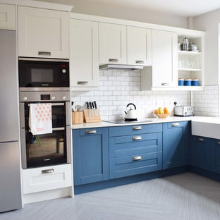 Photo of a mid-sized contemporary u-shaped eat-in kitchen in Other with a farmhouse sink, shaker cabinets, blue cabinets, recycled glass benchtops, white splashback, ceramic splashback, linoleum floors, a peninsula and grey floor.