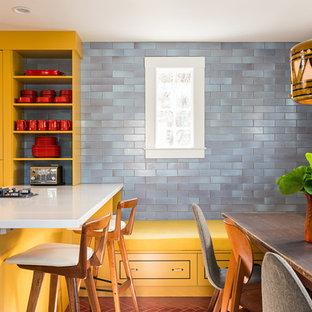 Idée de décoration pour une cuisine américaine design avec des portes de placard jaunes, un évier encastré, un placard à porte plane, une crédence bleue, un électroménager en acier inoxydable et un îlot central.