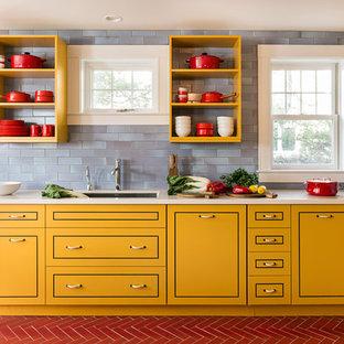 Inspiration för ett funkis l-kök, med en undermonterad diskho, gula skåp, blått stänkskydd, släta luckor, rostfria vitvaror och en köksö