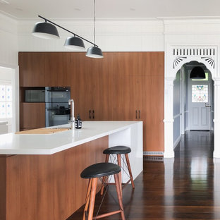 This is an example of a contemporary l-shaped kitchen in Brisbane with flat-panel cabinets, medium wood cabinets, black appliances, medium hardwood floors, with island, brown floor and white benchtop.
