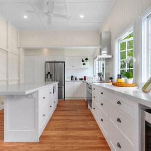 Design ideas for a country l-shaped kitchen in Brisbane with shaker cabinets, white cabinets, white splashback, window splashback, stainless steel appliances, medium hardwood floors, with island, brown floor and white benchtop.