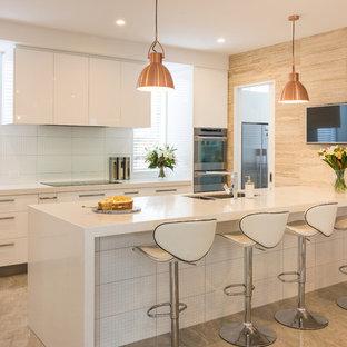 クライストチャーチの大きいモダンスタイルのおしゃれなキッチン (アンダーカウンターシンク、白いキャビネット、御影石カウンター、白いキッチンパネル、トラバーチンの床、シルバーの調理設備の、磁器タイルの床、ベージュの床) の写真