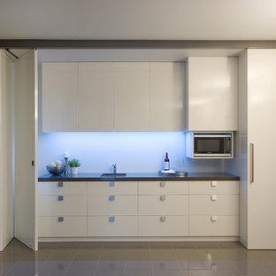 Foto på ett funkis linjärt kök, med släta luckor och vita skåp