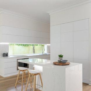アデレードのコンテンポラリースタイルのおしゃれなアイランドキッチン (ドロップインシンク、フラットパネル扉のキャビネット、ターコイズのキャビネット、ガラス板のキッチンパネル、淡色無垢フローリング、ベージュの床) の写真