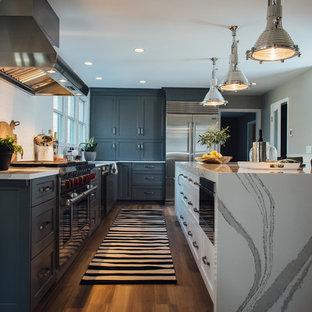 ボストンの広いモダンスタイルのおしゃれなキッチン (エプロンフロントシンク、シェーカースタイル扉のキャビネット、グレーのキャビネット、クオーツストーンカウンター、白いキッチンパネル、セラミックタイルのキッチンパネル、シルバーの調理設備、セラミックタイルの床、茶色い床) の写真