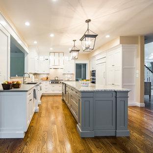 Geschlossene, Mittelgroße Klassische Küche in U-Form mit Unterbauwaschbecken, Schrankfronten im Shaker-Stil, Küchengeräten aus Edelstahl, dunklem Holzboden, Kücheninsel, weißen Schränken, Granit-Arbeitsplatte, Küchenrückwand in Beige und Rückwand aus Porzellanfliesen in Boston