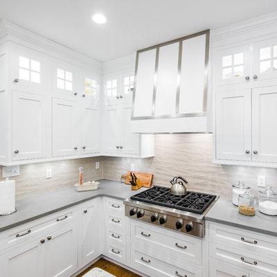 Mid-sized elegant u-shaped dark wood floor enclosed kitchen photo in Boston with an undermount sink, shaker cabinets, stainless steel appliances, an island, white cabinets, granite countertops, beige backsplash and porcelain backsplash
