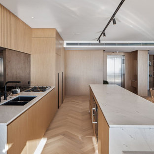 Design ideas for an expansive contemporary l-shaped open plan kitchen in Gold Coast - Tweed with medium wood cabinets, multiple islands, an undermount sink, flat-panel cabinets, black splashback, mirror splashback, beige floor and white benchtop.