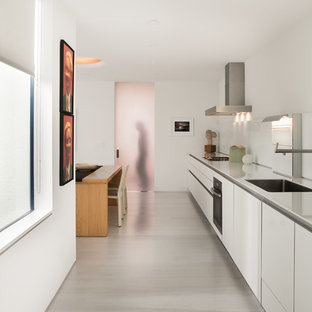 Design ideas for a large modern single-wall eat-in kitchen in San Francisco with flat-panel cabinets, white cabinets, light hardwood floors, no island, an integrated sink, stainless steel benchtops, white splashback, glass sheet splashback, stainless steel appliances and beige floor.