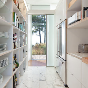This is an example of a modern galley separate kitchen in Seattle with stainless steel appliances, marble floors, flat-panel cabinets, white cabinets, wood benchtops and no island.