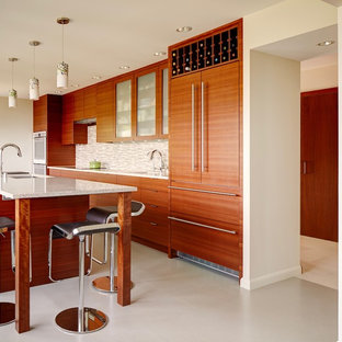 Design ideas for a large modern galley open plan kitchen in Seattle with a single-bowl sink, flat-panel cabinets, medium wood cabinets, recycled glass benchtops, glass tile splashback, white appliances, vinyl floors and with island.