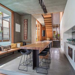 Modelo de cocina lineal, contemporánea, con fregadero bajoencimera, armarios con paneles lisos, puertas de armario blancas, suelo de cemento, una isla y suelo gris