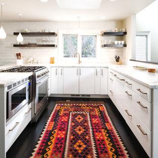 Foto de cocina en U, actual, con armarios con paneles lisos, puertas de armario blancas y salpicadero blanco