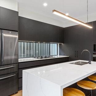 Moderne Küche mit Doppelwaschbecken, flächenbündigen Schrankfronten, schwarzen Schränken, Rückwand-Fenster, Küchengeräten aus Edelstahl, hellem Holzboden, Kücheninsel und weißer Arbeitsplatte in Adelaide