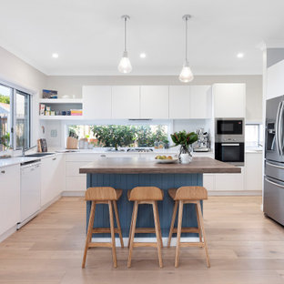 Inspiration for a contemporary u-shaped kitchen in Sydney with a double-bowl sink, flat-panel cabinets, white cabinets, wood benchtops, grey splashback, stainless steel appliances, medium hardwood floors, with island, beige floor and white benchtop.