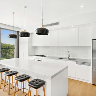 This is an example of a mid-sized contemporary single-wall open plan kitchen in Sydney with an integrated sink, flat-panel cabinets, white cabinets, stainless steel benchtops, white splashback, stainless steel appliances, medium hardwood floors, with island and brown floor.