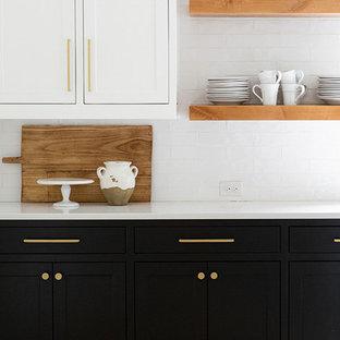 Réalisation d'une grande cuisine ouverte linéaire minimaliste avec un placard à porte shaker, des portes de placard noires, une crédence blanche, un sol en bois clair, un îlot central, un sol marron et un plan de travail blanc.