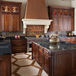Traditional kitchen in Dallas with granite benchtops, raised-panel cabinets, dark wood cabinets, brown splashback, matchstick tile splashback, stainless steel appliances and multi-coloured floor.