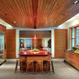 トロントの広いミッドセンチュリースタイルのおしゃれなキッチン (一体型シンク、フラットパネル扉のキャビネット、中間色木目調キャビネット、ステンレスカウンター、メタリックのキッチンパネル、シルバーの調理設備、磁器タイルの床、グレーの床、赤いキッチンカウンター) の写真