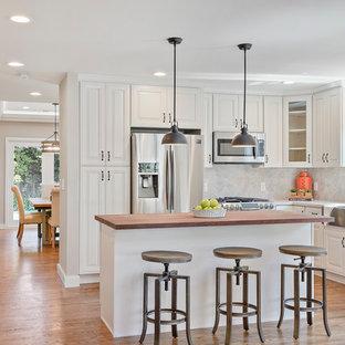 Bild på ett lantligt brun brunt l-kök, med luckor med upphöjd panel, vita skåp, träbänkskiva, grått stänkskydd, rostfria vitvaror, mellanmörkt trägolv, flera köksöar och brunt golv