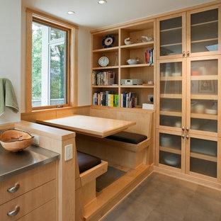 Modelo de cocina comedor de galera, contemporánea, sin isla, con armarios con paneles lisos, puertas de armario de madera clara, encimera de acero inoxidable y suelo de baldosas de porcelana