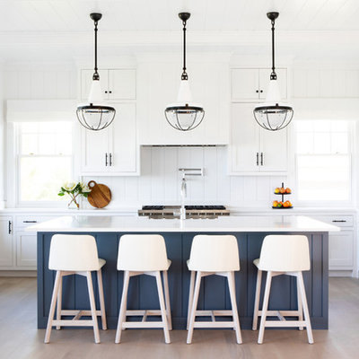 Large beach style u-shaped light wood floor and beige floor eat-in kitchen photo in New York with shaker cabinets, white cabinets, white backsplash, stainless steel appliances, an island, white countertops, a farmhouse sink, quartz countertops and wood backsplash
