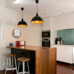 パースの中くらいのコンテンポラリースタイルのおしゃれなキッチン (フラットパネル扉のキャビネット、白いキャビネット、青いキッチンパネル、ガラス板のキッチンパネル、アンダーカウンターシンク、クオーツストーンカウンター、シルバーの調理設備、無垢フローリング) の写真