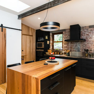 Inspiration for an industrial kitchen in Hobart with flat-panel cabinets, black cabinets, stainless steel benchtops, brick splashback, light hardwood floors, with island and beige floor.
