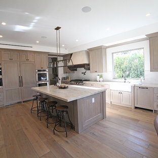 Photo of an expansive midcentury kitchen in Los Angeles with distressed cabinets, marble benchtops, white splashback, porcelain splashback, stainless steel appliances, medium hardwood floors, with island and brown floor.