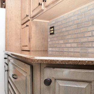 他の地域の中くらいのトランジショナルスタイルのおしゃれなキッチン (アンダーカウンターシンク、レイズドパネル扉のキャビネット、ベージュのキャビネット、珪岩カウンター、茶色いキッチンパネル、レンガのキッチンパネル、白い調理設備、セラミックタイルの床、ベージュの床、茶色いキッチンカウンター) の写真