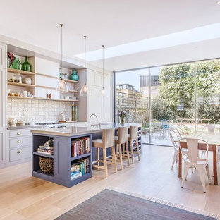 Design ideas for a large scandinavian single-wall kitchen/diner in London with a belfast sink, recessed-panel cabinets, grey cabinets, concrete worktops, white splashback, ceramic splashback, integrated appliances, light hardwood flooring and an island.